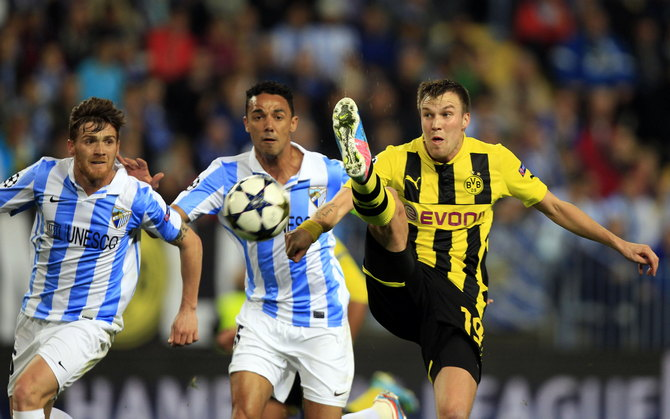 Borussia Dortmund's Grosskreutz goes for the ball against Malaga's Iturra and Demichelis during their Champions League quarter final first leg soccer match at La Rosaleda stadium in Malaga